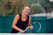 Tennis Player. Smiling Woman Playing Tennis, Cheerfully Laughing, Holds Racket And Ball. On The Court.