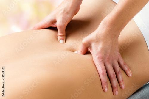 Therapist doing lower lumbar massage on woman.