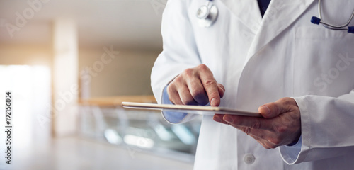 Fotografia Male doctor presses on screen digital tablet in the hospital