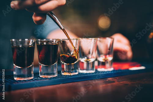 Fototapeta Bartender pouring and serving alcoholic drinks at bar