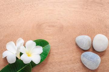 Fototapeta na wymiar Frangipani or Plumeria  flower and stone zen spa on wooden plank