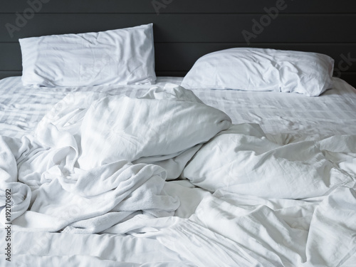 Messy White Bedding Sheets And Pillow In Bedroom Background ,Unmade Messy  Bed After Comfort Sleep
