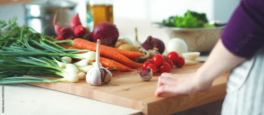 Fototapeta Young Woman Cooking in the kitchen. Healthy Food