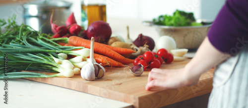 Obraz Young Woman Cooking in the kitchen. Healthy Food - fototapety do salonu