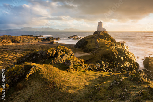 Tuinposter Kust Llanddwyn Island Lighthouse with beautiful evening golden light after a rain storm.