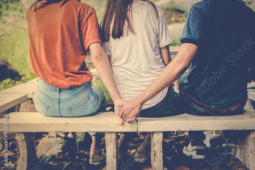 Photo Boyfriend and another woman grab hands from behind together without sight of his girlfriend