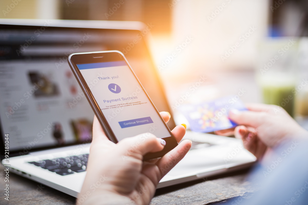 Fototapeta Online shopping concept, young woman hands holding using mobile smart phone and credit card making online payment with laptop computer on table while holiday