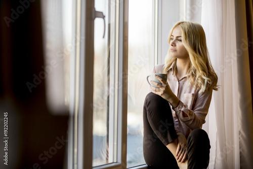 Fotografie, Obraz  Blonde young woman drinking coffee by window