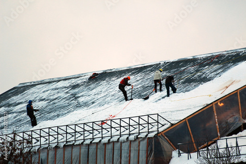 Fotografiet  mountain climbers cleaning the snow from the roof