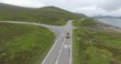 Cinematic aerial of vehicle on country highway over captivating highlands