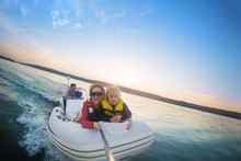 Happy Couple With Daughter Riding Boat On Lake Or River At Sunset. Pair  With Child Making Selfie While Water Activity.  Happy Family  Recreation And Adventure Concept. Beautiful Travel Background