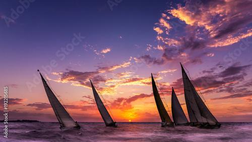 Fotografia  des voiliers naviguent au soleil couchant