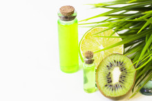 Lime And Kiwi Oil Skin And Hair Care Home Spa. Bottles Of Oil, Green Leaves. White Board Background