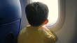 Little boy looking out the airplane window