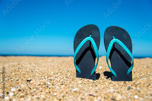 blue flip-flops on the sand - a concept for summer vacation, travel and leisure