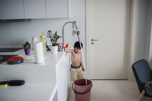 Shirtless Boy Filling Water In Bucket At Home
