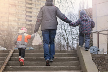 Rear view of father and two kids holding hands while walking on the street