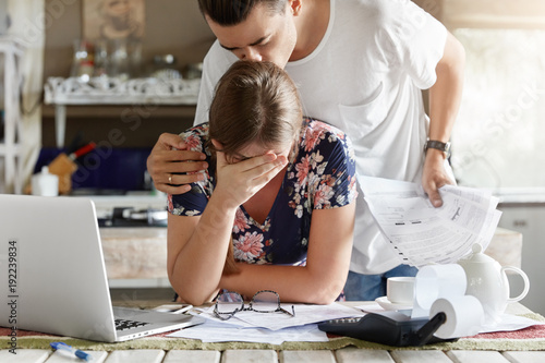 Photo of unhappy young woman has problems, works with papers and modern laptop computer, calculate financial debts. Family couple manage finances at kitchen together, have sorrorful expressions