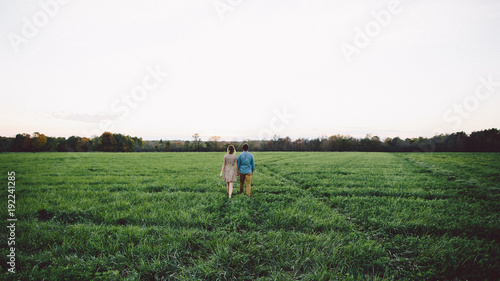 Rear view of couple holding hands while walking in a grassy field