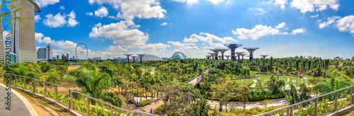 panoramaaufnahme-von-erhohtem-standpunkt-uber-die-gardens-by-the-bay-in-singapur-mit-riesenrad-und-supertrees-fotografiert-tagsuber-bei-blauem-himmel-mit-lockeren-wolken-im-marz-2015