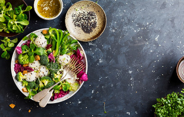 Fresh salad with rice and vegetable on dark background top view with space for text. Healthy food.