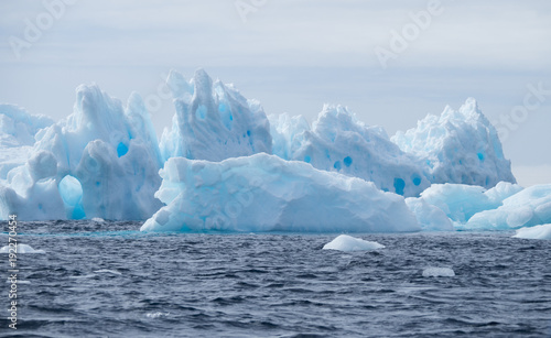 Fotobehang Antarctica Light turquoise blue iceberg with crevices, cracks, holes and fissures floating in the dark blue Southern Ocean in Antarctica.