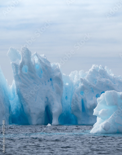Poster Antarctique Iceberg with light and medium turquoise blues in a deep blue Southern Ocean. Cloudy sky is above. The icebergs have fissures, crevices and caves.