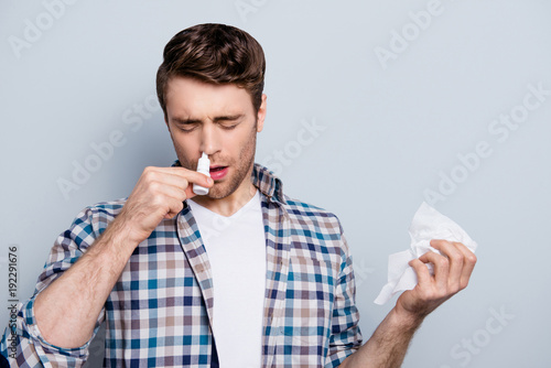 Photo  Portrait of attractive guy with a nasal spray and tissue in hands, using nose dr