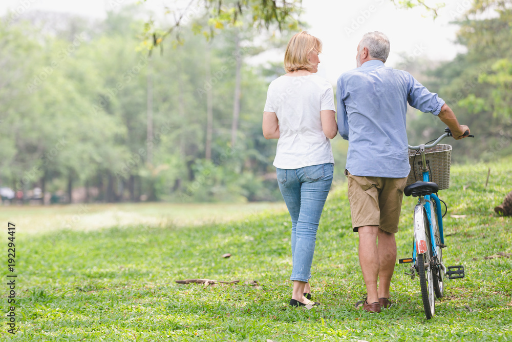 Fototapeta Leisure lifestyle,Senior couple walking their bike along happily talking in the park, rear view of an older caucasian walk in a park