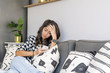 Portrait of Beautiful Sad Woman Using Mobile Phone at Home
