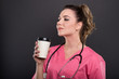 Side view of beautiful young doctor holding takeaway coffee