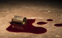 Empty Handgun Brass With Blood On A Beige Floor Tile