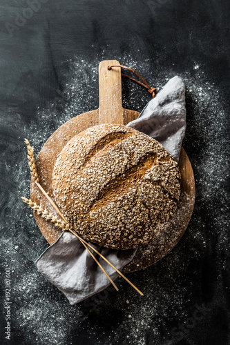 Cuadros en Lienzo Bakery - round loaf of rustic bread on black background