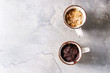 Chocolate and vanilla caramel mug cakes from microwave over grey texture background. Top view, copy space