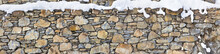 Verschneite Natursteinmauer