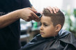 Professional hairdresser uses a hair clipper for fringing hair for a small boy