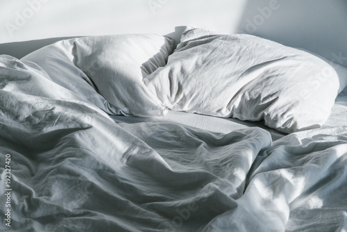 Vászonkép crumpled bed on sunrise sun lights