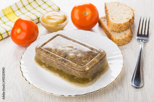 Photo Meat aspic in plate, napkin, tomatoes, mustard, bread and fork