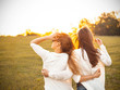 canvas print picture Two young women are looking forward tothe sunset outdoors