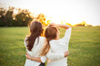 canvas print picture Two females are looking forward to the sunset on the green field.