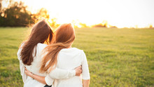 Young Women In White Sweaters Are Walking On The Green Field. Best Friends