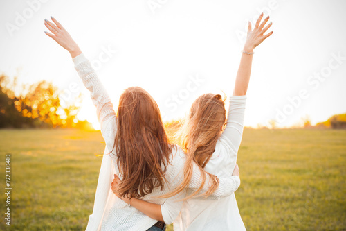 Obraz Young women are having fun on the green field in the evening. - fototapety do salonu