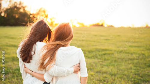 Photo  Young women in white sweaters are walking on the green field