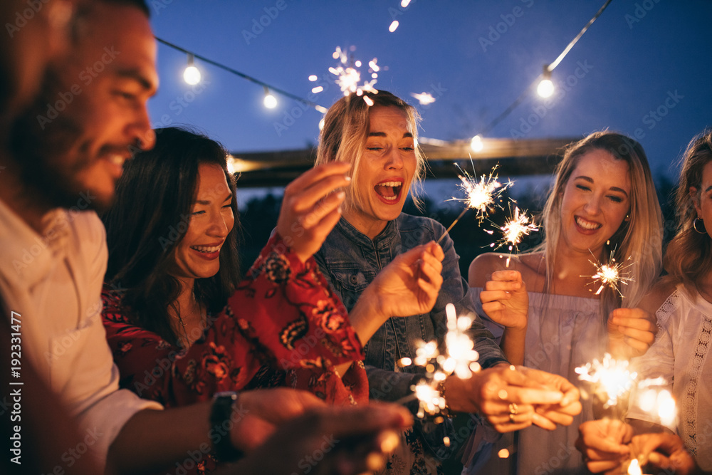 Fotografía Group of friends with sparklers enjoying outdoor party