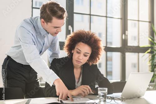 Obraz na płótnie Supervisor checking business statistics and explaining the results to a colleagu
