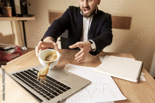 Fotografija  Coffee in white cup spilling on the table in the morning working day at office t