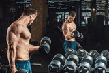 Good looking young man lifting dumbbells and working on his biceps in front of a mirror looking on his biceps