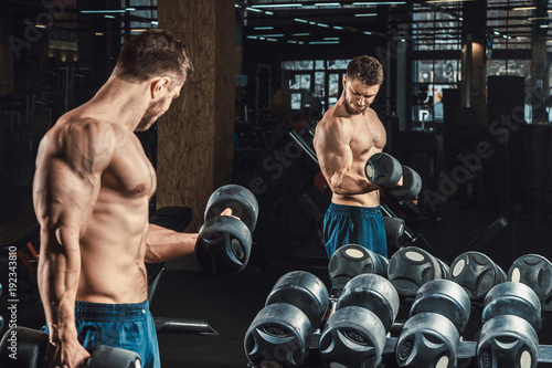 Good looking young man lifting dumbbells and working on his biceps in front of a Poster Mural XXL