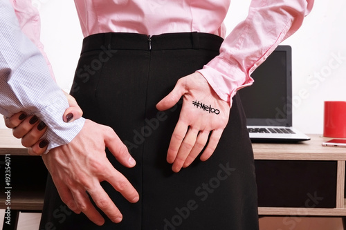 Fotografía  Boss man shows inappropriate behavior towards young woman at workplace desk