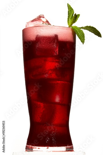 Red juice with ice cubes and mint garnish on white background